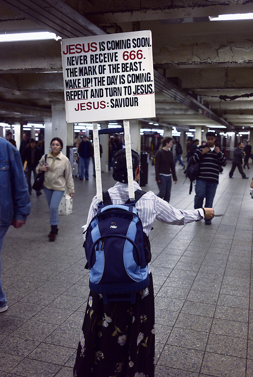 Woman handing out religious pamphlets, Times Square subway station