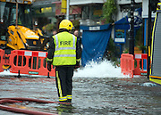 © Licensed to London News Pictures. 06/10/2014. Twickenham, UK Firefighters help to contain a mains water pipe which has burst in King Street Twickenham today 6th October 2014. It appears that workmen working in the area have used a JCB digger to stem the flow. Many local shops and businesses have been flooded.   Photo credit : Stephen Simpson/LNP