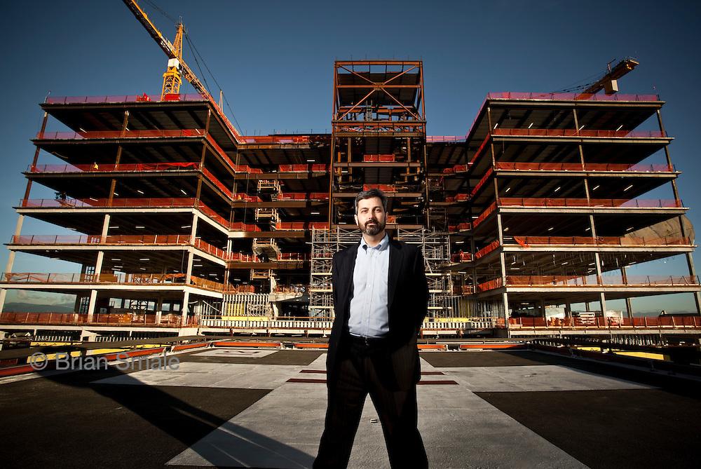 CEO Dave Brooks, on helipad of hospital.  New hospital constructino in background.
