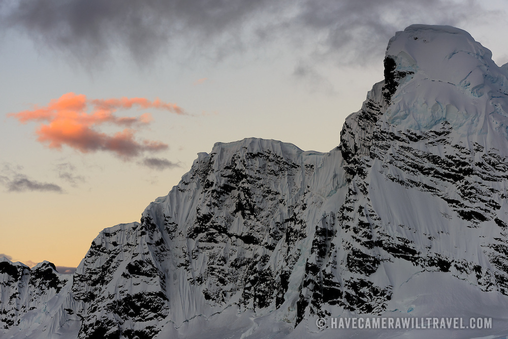 The setting sun catches its golden rays on a cloud above an icy and rocky mountain range at Paradise Harbor, Antarctica.