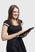 Portrait of young woman using tablet PC over gray background