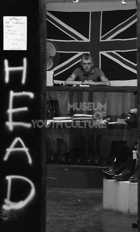 Skinhead behind counter, London shop, 1980s.