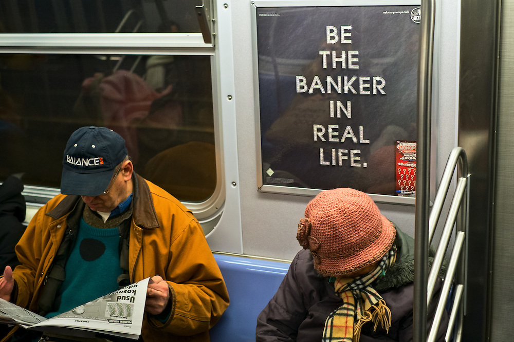 "Subway riders and advertisement reading ""Be the banker in real life"", New York, NY, US"