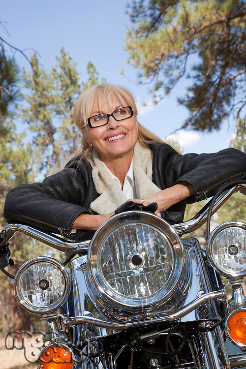 Senior woman leaning on motorcycle handlebars in a forest