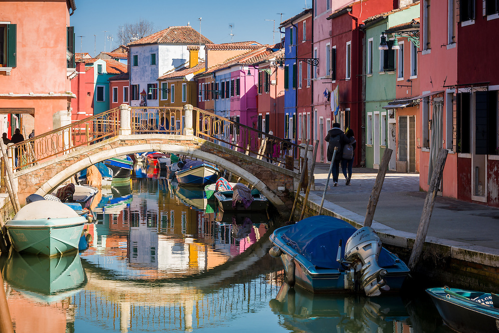 traditional houses lining the canal in burano can be seen painted in bright colours