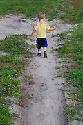 A small boy walks away on a sandy path.