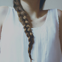 faceless portrait of a girl with pale light and braided hair