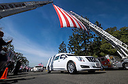 The hearse carrying the body of Whittier Police Officer Keith Boyer passes under a giant U.S. flag at Rose Hills Memorial Park in Whittier, Calif., Friday March 3, 2017. Boyer, who was fatally shot after responding to a traffic crash, was remembered today by thousands of law enforcement officers, friends and family as a dedicated public servant, talented drummer, loving friend and even a ``goofy'' dad.<br />
