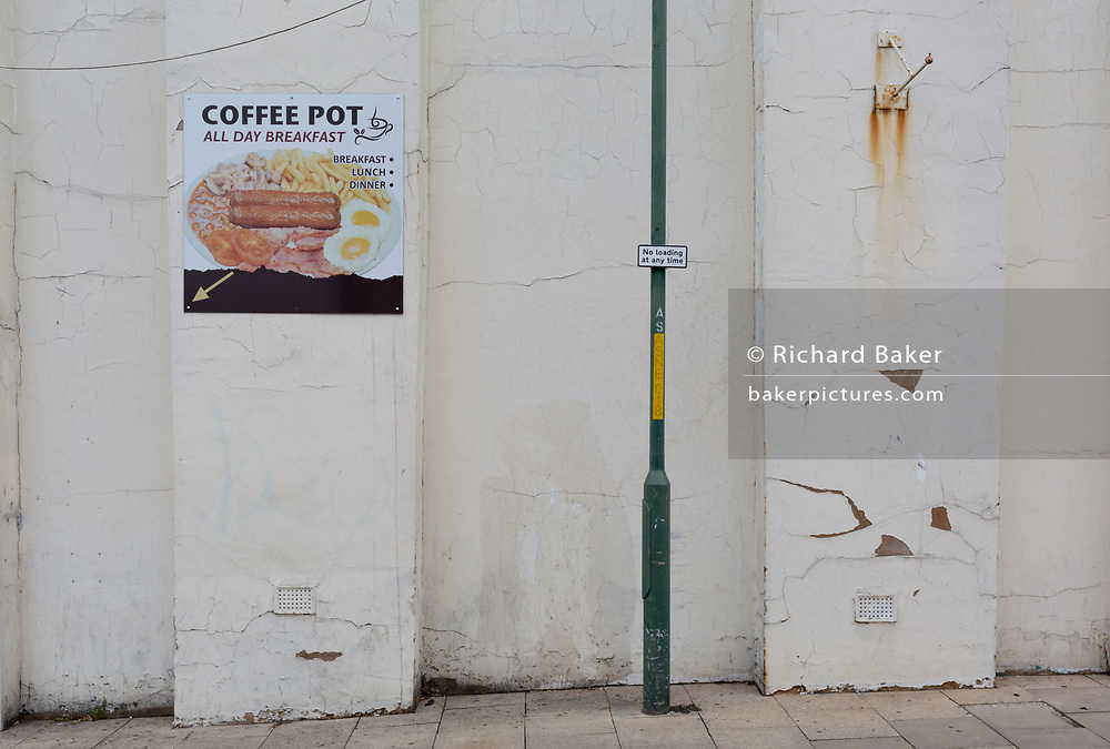 A wall landscape of cracked and peeling plaster and a poster for an all-day breakfast cafe called the Coffee Pot located around the corner, on 3rd October 2019, in Dartford, Kent, England. Voters in Dartford voted 64% in favour of Brexit during the 2016 referendum.