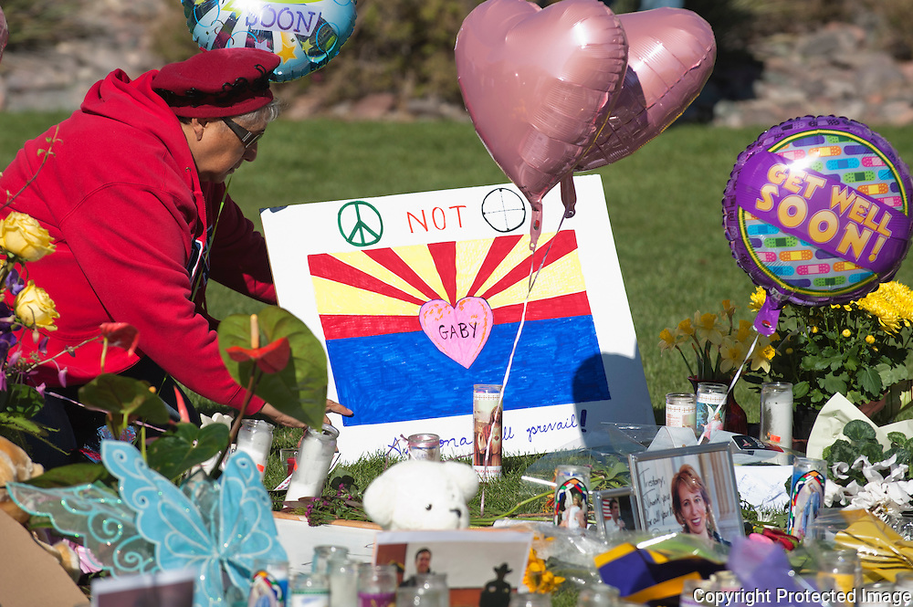 A visitor to the memorial places a poster inviting peace. Located at the memorial in front of the University of Arizona Medical Center in Tucson, Arizona. The memorial was placed for the victims of the recent shooting in Tucson.