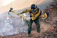 "A woman on the Chuchupati Flight Crew 530 uses her ""Pulaski"" tool to clear a circle around a spot fire that jumped over the fire break at the La Brea Fire."