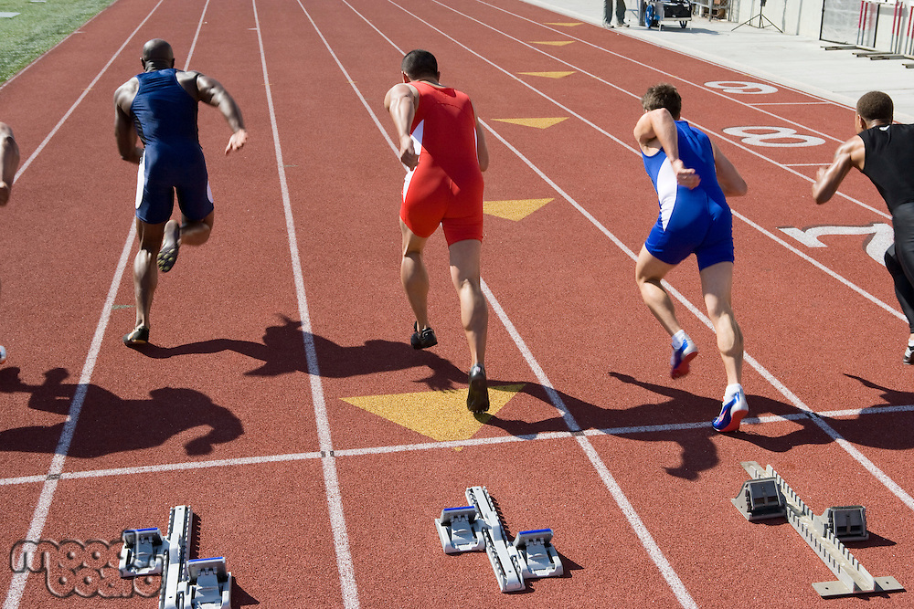 Athletes starting to run, rear view