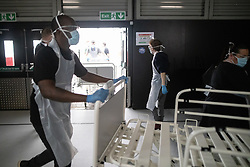 © Licensed to London News Pictures . 21/04/2020. Manchester, UK. A porter pushes a bed in to the rear of the hospital , where it will be cleaned before being placed on the ward . The National Health Service has built a 648 bed field hospital for the treatment of Covid-19 patients , at the historical railway station terminus which now forms the main hall of the Manchester Central Convention Centre . The facility is treating patients from across the North West of England , providing them with general medical care and oxygen therapy after discharge from Intensive Care Units . Photo credit : Joel Goodman/LNP