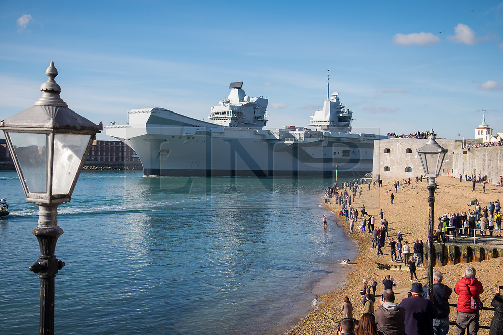 © Licensed to London News Pictures. 30/10/2017. Portsmouth, UK.  Crowds gather to watch the Royal Navy's flagship, HMS Queen Elizabeth, as she departs Her Majesty's Naval Base (HMNB) Portsmouth for the first time since her arrival on 16/08/2017.  The new aircraft carrier is heading back to sea for the second stages of her sea trials.<br /> <br /> Flight trials involving the new F-35B Joint Strike Fighter are expected to take place off the coast of the U.S. next year, and she is due to come into service in the early 2020s.  Photo credit: Rob Arnold/LNP