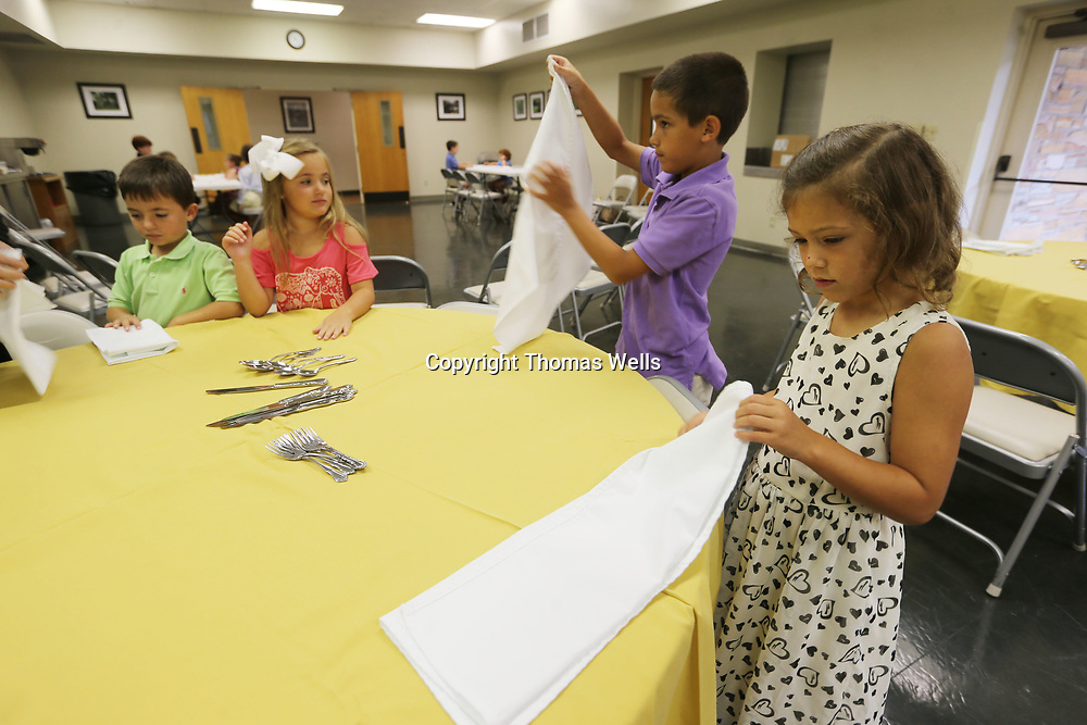 Lexi Oliver begins to fold napkins as she and her classmates get ready to learn how to ste up a dinning room table during as etiquette class.