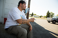 Jason Hill smokes a cigar before he starts his shift at the convienece store he works at in the Hillyard area of Spokane, Wash. on Friday, July 24, 2015.