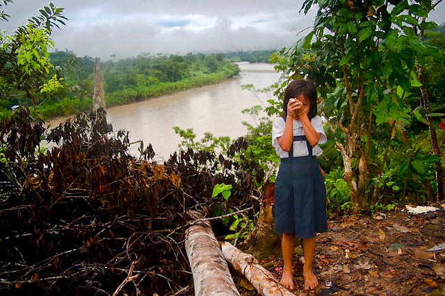 "A awajun native child wearing school«s uniform posses for a portrait near to Imaza river-port of the Mara-on river in Amazons district, Peru. After the events of June 5 in the Amazonian province of Bagua, in northeastern Peru, where 24 policemen and a number still not confirmed of natives from the communities of the ÒAlto Mara-onÓ and civilians died in clashes after a series of demonstrations in opposition to the approval by the Peruvian government, for a group of ordinances that allow large flexibility in the restrictions on resource extraction in the area, breaking the 169 agreement of ILO (International Labour Organization), which requires the consultation of indigenous communities about the exploitation of nature in their territories. One of the most active communities was the awajun, a warlike and revengeful people, heritors of the Jibaros and recently contacted near to 1950. For the leader or ""apu"" for one of the aguarunas riverside communities of the Mara-on, Simon Weepiu, Òthe force of this movement come from the conviction of the struggle, which is caused by the ancestral development as based on worldview, which provides the native of a special power, that of becoming one with his idea and his brothers, to focus all on the same objective and be just a great strength."" The government aims to generate development in the area allowing the exploitation of property, The jungle is rich in gold and oil, and even argue that natural wealth of the region belong to all Peruvians, and not just the communities that inhabit it, but acts as the oil«s filtration to waters of the Mara-on, left in evidence that in a complex ecosystem like jungle that mixed spilled oil by rain in the river, home to fishes, as well as the waters that irrigate cassava, bananas, sugarcane and other elements vital to the development of communities. The natives, insist that the forest is not only home, is where they get medicines to cure their sick and food for their families. The pre-existence an"