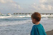 A small boy watches the waves breaking on the beach on a windy afternoon in Lake Worth, Florida.