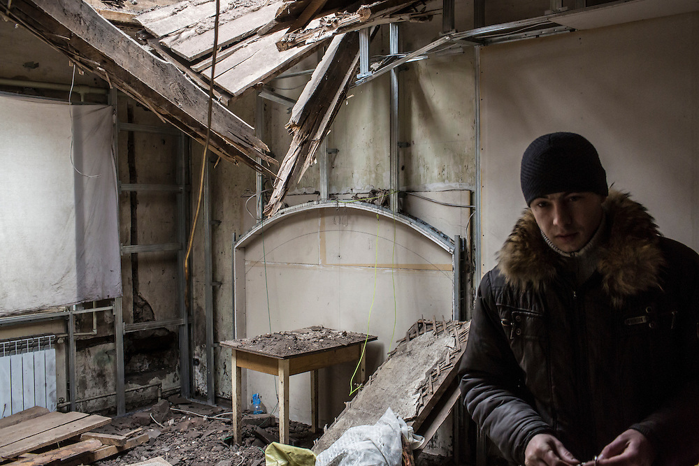 DONETSK, UKRAINE - JANUARY 29, 2015: Aleksandr Dynya, 31, shows the apartment of a neighbor which was destroyed when a shell fell through the roof in the Petrovskyi district of Donetsk, Ukraine. The neighborhood has been shelled heavily in the past few days as fighting between Ukrainian forces and pro-Russia rebels has flared. CREDIT: Brendan Hoffman for The New York Times