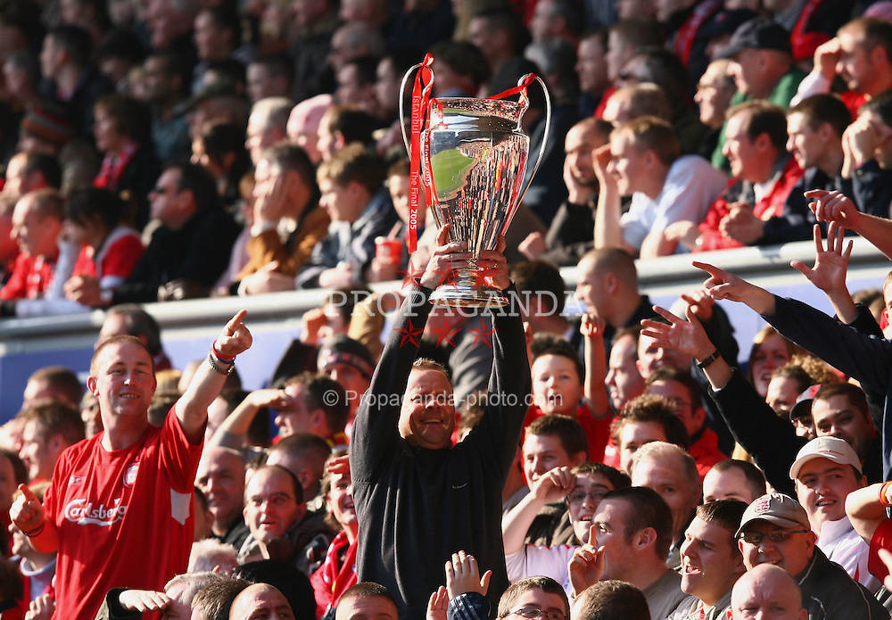 LIVERPOOL, ENGLAND - SATURDAY, FEBRUARY 18th, 2006: 'We won it five times...' A Liverpool fan holds aloft a copy of European Champions League Cup during the FA Cup 5th Round clash between Liverpool and Manchester  United at Anfield. (Pic by David Rawcliffe/Propaganda)