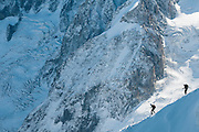 Photo of alpinists descenting Aiguille du Mide on a steep ridge towards Vallee Blanche