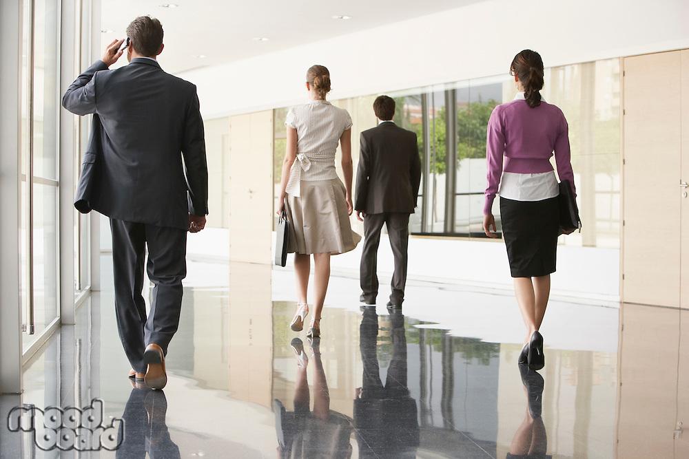 Four Businesspeople Walking in Office Corridor