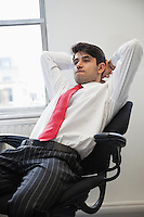 Young Indian businessman contemplating while sitting in office chair