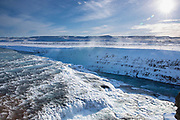 Gushing glacial river water at falls of Gullfoss Waterfall and mountains in glacial landscape of South Iceland