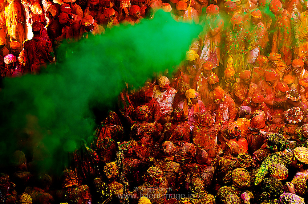 Samaj at Radha Rani temple, Barsana. People sing loudly in a very colorful environment. Dry and wet colors splashed on them from all corners of the temple. A cloud of green color approaching. Braj ki Holi