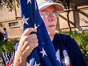 """11 NOVEMBER 2013 - PHOENIX, AZ:  A woman holds an American flag while she watches the Phoenix Veterans Day Parade. The Phoenix Veterans Day Parade is one of the largest in the United States. Thousands of people line the 3.5 mile parade route and more than 85 units participate in the parade. The theme of this year's parade is """"saluting America's veterans.""""    PHOTO BY JACK KURTZ"""