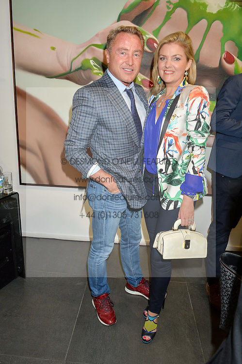 MICHAEL FLATLEY and his wife NIAMH at a private view of woks by German artist Mike Dargas held at the Opera Gallery, 134 New Bond Street, London on 5th July 2016.
