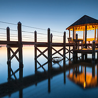A wooden boardwalk and covered gazebo stretch out into the Pamlico Sound in Hatteras, North Carolina as the blue hour of evening descends on a calm Pamlico Sound.  Hatteras is part of a chain of barrier islands off the coast of North Carolina known as the Outer Banks (OBX).