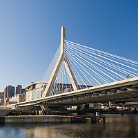 """The Leonard P. Zakim Bunker Hill Memorial Bridge (or Zakim Bridge) is a cable-stayed bridge across the Charles River in Boston, Massachusetts. It is a replacement for the Charlestown High Bridge, an older truss bridge constructed in the 1950s, and is the world's widest cable-stayed bridge. Of 10 lanes, the main portion of the Zakim Bridge carries four lanes each way (northbound and southbound) of the Interstate 93 and U.S. Route 1 concurrency between the Thomas P. """"Tip"""" O'Neill Jr. Tunnel and the elevated highway to the north. Two additional lanes are cantilevered outside the cables, which carry northbound traffic from the Sumner Tunnel and North End on-ramp. These lanes merge with the main highway north of the bridge. I-93 heads toward New Hampshire as the """"Northern Expressway"""", and US 1 splits from the Interstate and travels northeast toward Massachusetts' north shore, crossing the Mystic River via the Tobin Bridge.<br /> <br /> The bridge and connecting tunnel were built as part of the Big Dig, the largest highway construction project in the United States. The north-bound (NB) lanes were finished in March 2003, then south-bound (SB) lanes in December. The bridge's unique styling quickly became an icon for Boston, often featured in the backdrop of national news channels, to establish location, and included on tourist souvenirs. The bridge is commonly referred to as the """"Zakim Bridge"""" or """"Bunker Hill Bridge"""" by residents of nearby Charlestown. Wikipedia"""