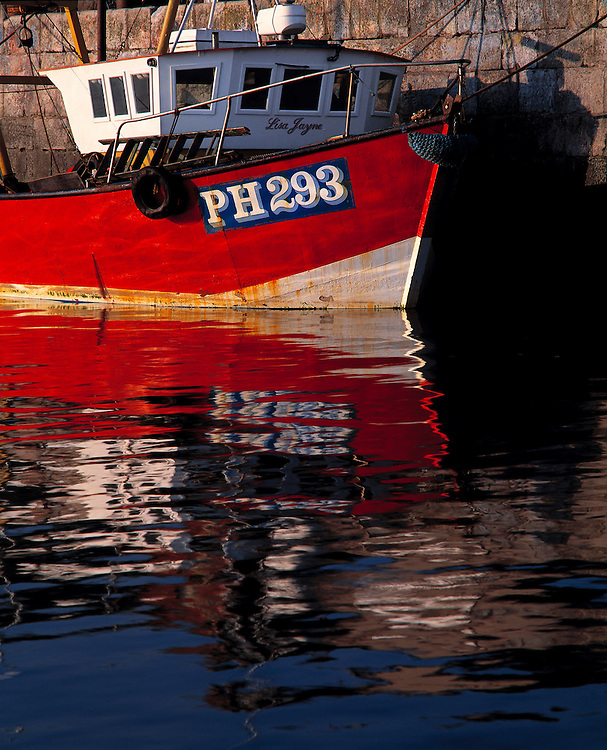 A fishing boat is reflected in the water at Conwy, Gwynedd County, Wales.
