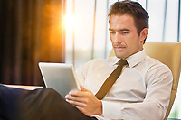 Thoughtful businessman using digital tablet while sitting with lens flare