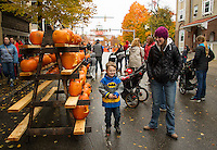 Colten Goss checks out the pumpkins lining Main Street in Laconia during Saturday's Pumpkin Fest.  (Karen Bobotas/for the Laconia Daily Sun)
