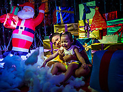 "23 DECEMBER 2018 - CHANTABURI, THAILAND: Siblings play cotton balls the represent snow in the ""North Pole"" at the Cathedral of the Immaculate Conception's Christmas Fair in Chantaburi. Cathedral of the Immaculate Conception is holding its annual Christmas festival, this year called ""Sweet Christmas @ Chantaburi 2018"". The Cathedral is the largest Catholic church in Thailand and was founded more than 300 years ago by Vietnamese Catholics who settled in Thailand, then Siam.   PHOTO BY JACK KURTZ"