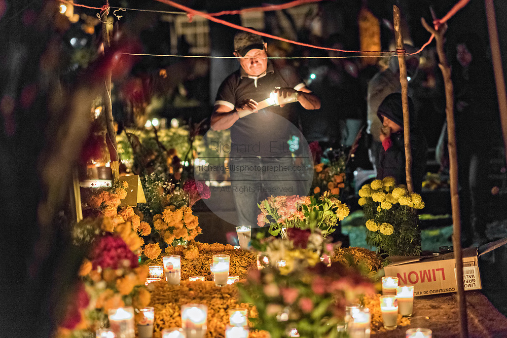 A man lights candles around the gravesite of a family member during the Day of the Dead festival October 31, 2017 in Tzintzuntzan, Michoacan, Mexico.