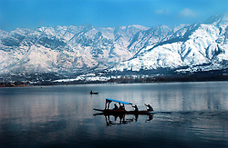 "Kashmiris take a Sunday afternoon ""shikari""  or gondola on Dal Lake with the Himalayas as a backdrop in Srinigar, February 10, 2002 in the Indian held state of Kashmir. India and Pakistan have already fought three wars over Kashmir and are the brink again as they amass their troops along the Line of Control. (Ami Vitale/Getty Images)"