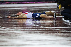 London, August 09 2017 . Karsten Warholm, Norway, lies on the rain-soaked track after becoming world champion in the men's 400m hurdles final  on day six of the IAAF London 2017 world Championships at the London Stadium. © Paul Davey.