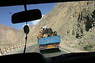 "Uygur ethnic minority travelers and camels are seen comfortably riding together in the back of a truck along the Karakoram Highway from Kashgar towards Karakul lake in China's Xinjiang autonomous region, Monday May 22. 2006. ""China, the United Nations and neighboring Central Asian countries plan a program aimed at reviving the ancient Silk Road by boosting investment, trade and tourism. The two-year Silk Road Project involves the governments of China, Kazakhstan, Kyrgyzstan, Tajikistan and Uzbekistan. Winding more than 9,600 kilometers (6,000 miles) through desolate mountains and deserts, the Silk Road guided camel caravans to and from Central Asia and Europe. Marco Polo, Genghis Khan and Alexander the Great followed its paths."""