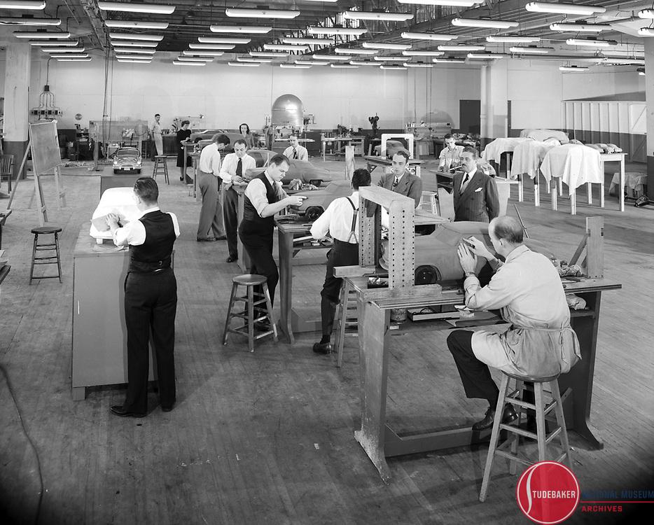 "The Studebaker Design Department c. 1945.  L-R:  Holden ""Bob"" Koto, Larry Brom (far rear), Virginia Spence (black dress), Vince Gardner, Robert Bourke (facing camera, necktie), Nancy Spence, Frank Alroth (vest), Jack Aldrich, John Reinhart (suspenders), Virgil Exner, John Bird, Raymond Loewy, Gordon Buehrig (seated on stool)."
