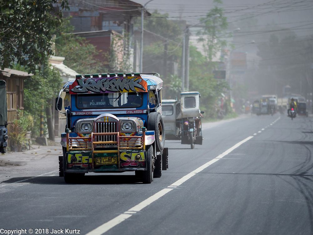 30 JANUARY 2018 - GUINOBATAN, ALBAY, PHILIPPINES: Traffic in Guinobatan during an ash fall caused by Mayon volcano. The volcano continued to erupt but not as dramatically as it did last week. The small eruptions are still sending ash clouds over communities west of the volcano and the government is encouraging people to stay indoors, wear face masks and avoid strenuous activities when ash is falling.     PHOTO BY JACK KURTZ