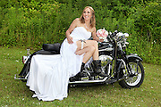 Bride wearing black leather boots holding her pink rose bouquet sitting on a Harley Davidson motorcycle, Syracuse, NY