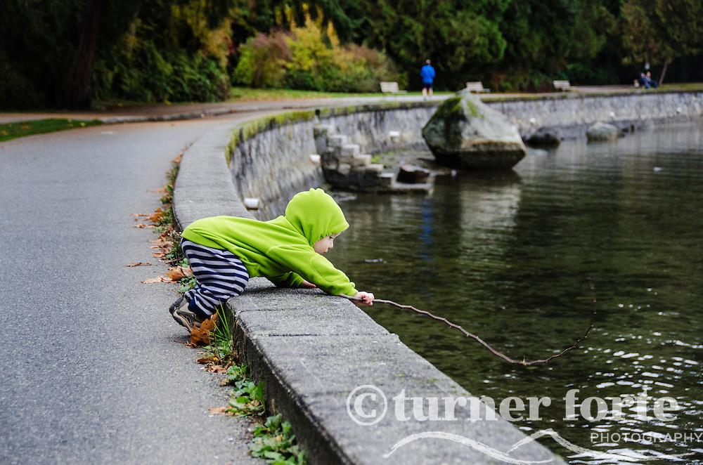 Toddler boy pretend fishing with a stick on the waterfront in Vancouver, Canada.
