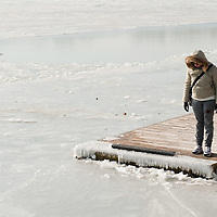 VENICE, ITALY - FEBRUARY 05: A woman looks at the frozen Venice Lagoonl on February 5, 2012 in Venice, Italy. Italy as most of Europe is under a spell of very cold weather, it is more than 20 years aince the Venice Lagoon last froze.  (Photo by Marco Secchi/Getty Images)