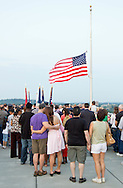 Highland, New York - People watch as the flag is lowered to half-staff during a Memorial Day ceremony at the center of the Walkway over the Hudson on May 27, 2012.