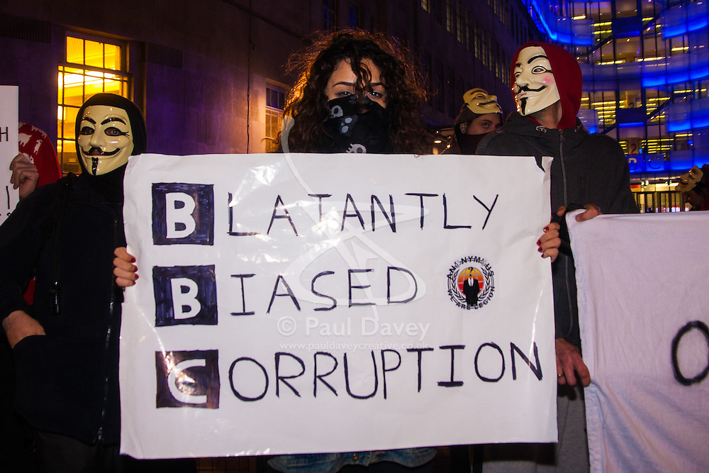 """London, December 23rd 2014. Online activism group Anonymous march through London from the City to the BBC's HQ on Great Portland Street in protest against alleged biases and coverups of a """"paedophile ring"""". PICTURED: A young woman poses with her placard for the """"Blatantly Biased Corruption"""" outside the BBC's Portland Place offices."""
