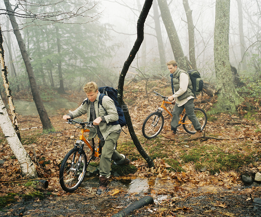 Two men walking in the wood with their mountain bikes