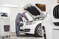 Full length of male engineer examining car in automobile repair shop